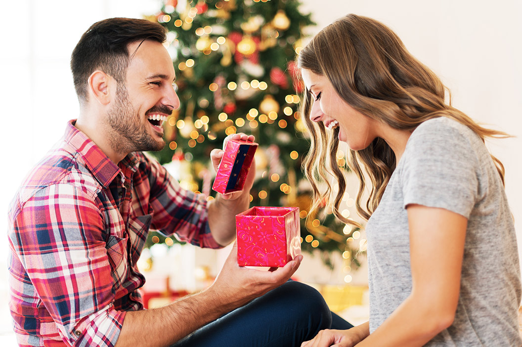 couple opening gifts in front of christmas tree