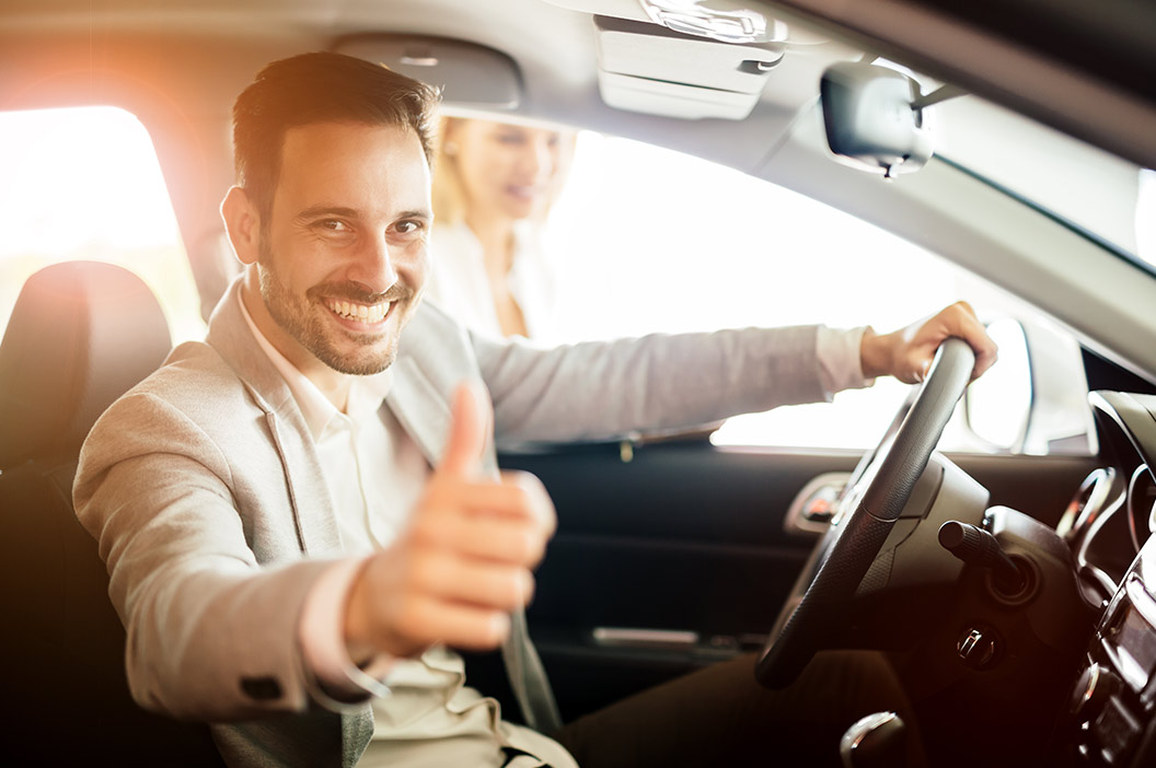 man driving with thumb up